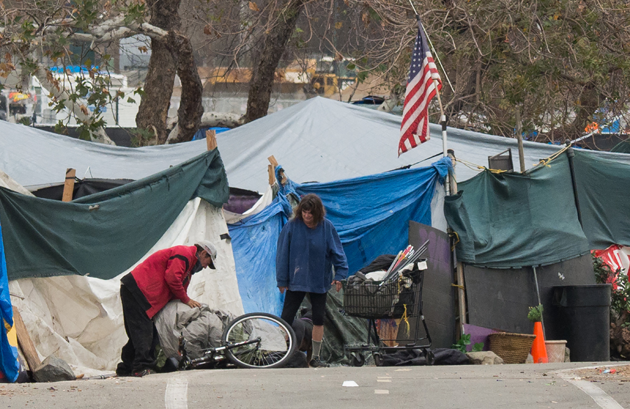 A homeless enc&ment made of tents and tarps lines the Santa Ana riverbed in Anaheim California on Jan 25 2018. ROBYN BECK / AGENCE FRANCEPRESSE & Tensions simmer in tent cities - USA - Chinadaily.com.cn