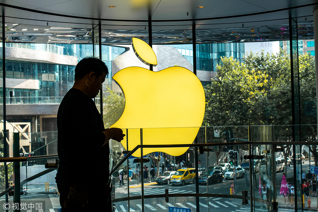 A customer stands beside an illuminated Apple logo at an Apple store in Shanghai on Aug 6 2018