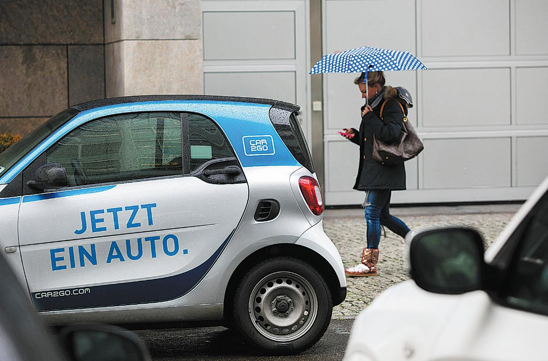 A Pedestrian Shelters Under An Umbrella As He Pes Parked Daimler Ag Smart Fortwo Car2go Car Sharing Automobile In Berlin Germany Photo Agencies