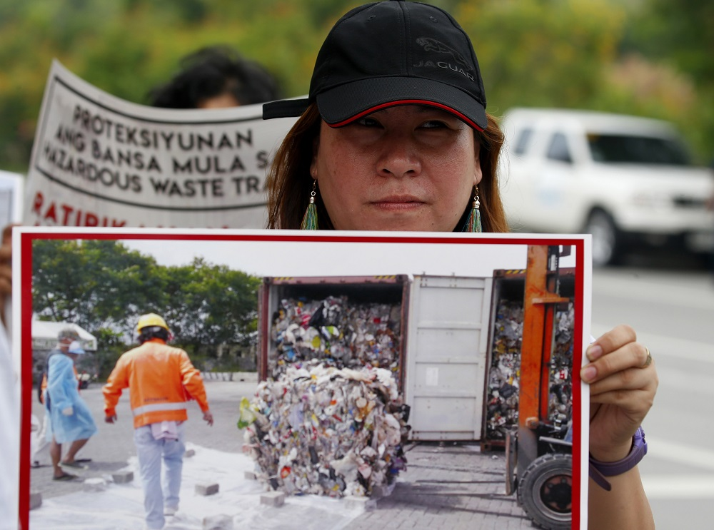 An environmentalist displays a photo of a container of garbage from Canada at a protest in May at the Philippine Senate to demand the Canadian government remove the garbage shipped to the country six years ago in suburban Pasay city, south of Manila. Image: BULLIT MARQUEZ/ASSOCIATED PRESS